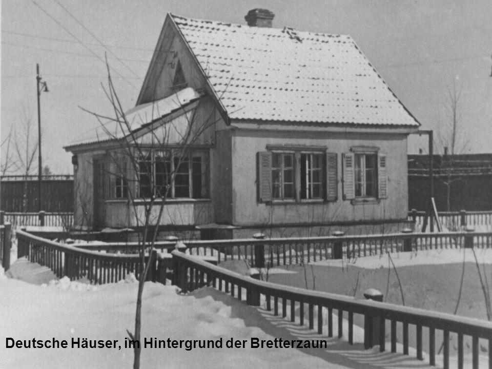 Deutsche Häuser, im Hintergrund der Bretterzaun
