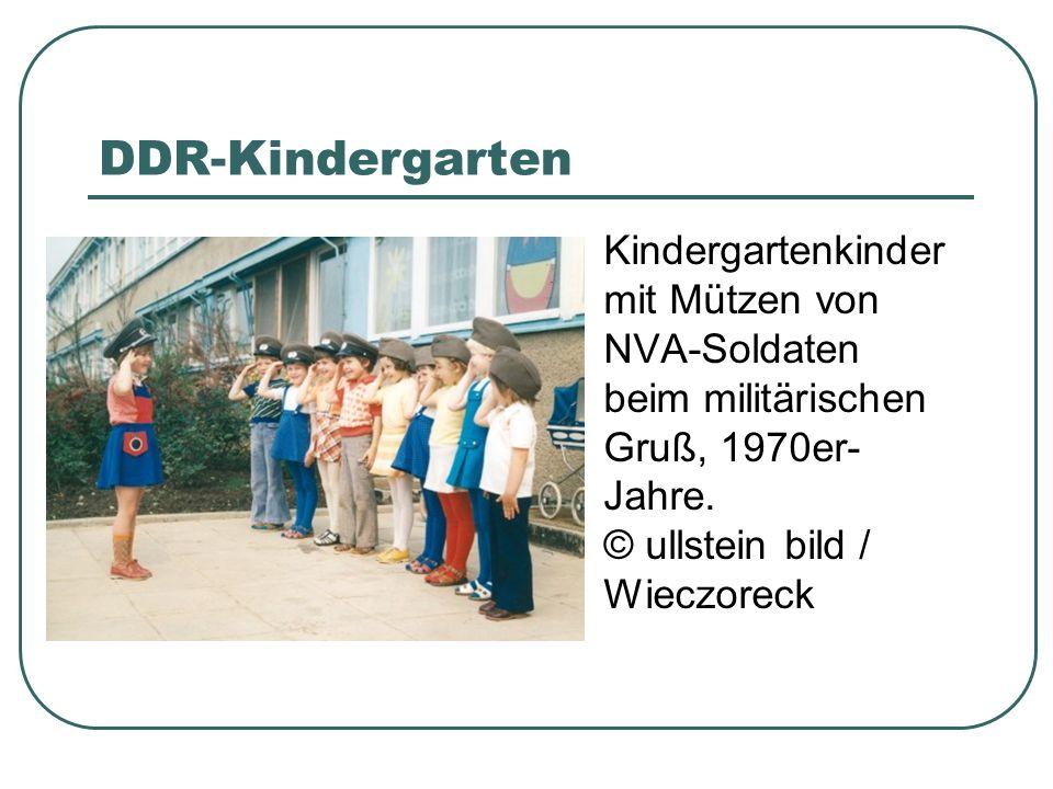 DDR-Kindergarten Kindergartenkinder mit Mützen von NVA-Soldaten beim militärischen Gruß, 1970er- Jahre.